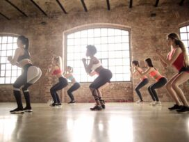 The group of women performs butt and thigh workout.